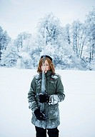 Sweden, girl 8_9 covered with snow in holding icacle in winter scenery
