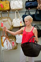 Young woman shopping and comparing different nylon shoulder bags in store