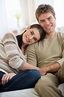 Portrait of happy couple sitting on sofa