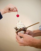 Close up of hands of grandfather and grandson 8_9 holding icecreame and cherry