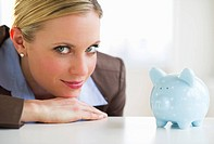 Portrait of businesswoman with piggy bank