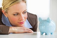 Businesswoman looking at piggy bank