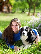 USA, Colorado, Portrait of young woman embracing dog on grass