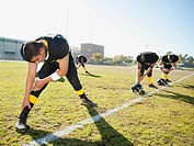 Football players stretching on football field
