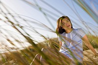 USA, California, Point Reyes, Young woman sitting in grass on sand dune