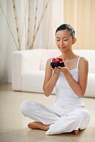 Woman sitting on the floor with her eyes closed while holding a wooden bowl with flower petals