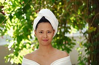 Woman with hair wrapped in towel, looking at the camera