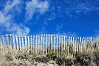 Wooden picket fence on sand dune with blue sky, France, Europe