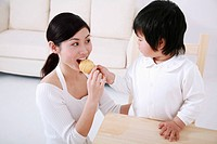 Girl feeding woman with cookie