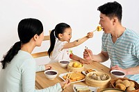 Girl feeding man dim sum using chopsticks