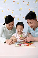 Man and woman helping girl to complete the map puzzle
