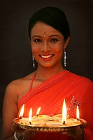Woman holding a tray of lit oil lamps, smiling