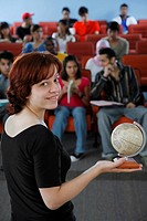Woman holding a globe looking at the camera with students in the background