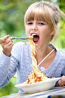 girl eating spaghetti in the garden