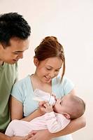 Woman feeding baby with milk, man watching