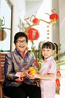 Senior woman receiving some mandarin oranges from girl