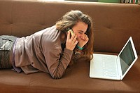Teen girl with laptop computer and cell phone