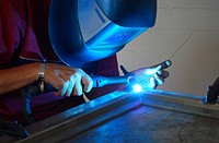 welder welding a piece of steel with blue light