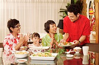 Man serving food, woman together with girl and senior woman clapping hands while watching