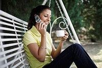 Woman enjoying a cup of coffee while talking on the phone