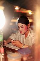 Opera performer using mobile phone