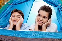 Girl with her brother lying in a tent