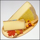 Mon Poligny Comté French cheese and slice on wooden board