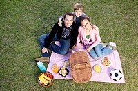 Portrait of a couple enjoying picnic with their son
