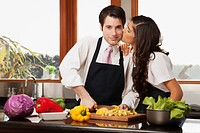 Man preparing food with his wife kissing him