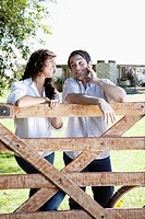 Couple leaning against a wooden fence in a field