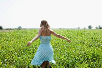 Woman kneeling in a field with her arm outstretched
