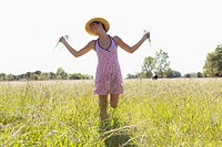 Woman holding plants and running in a field
