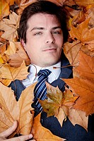 Businessman lying on maple leaves