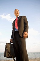 Businessman standing on the beach and smiling