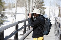 Man photographing in a forest, Yellowstone National Park, Wyoming, USA