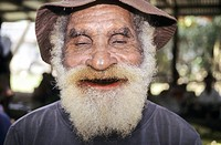 Betel nut user. Elderly man displaying the red mouth that characterises inveterate betel nut chewers. Betel nuts, from the betel nut palm tree Arecha ...