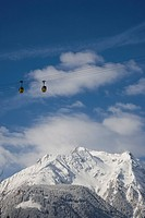 Cable cars hang high above the snowy ground near Mayrhofen, Austria.