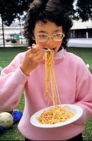 mid shot of a young girl in park obviously enjoying her bowl of spaghetti