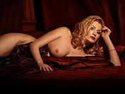 Glamour photo of a naked woman in her thirties lying in bed
