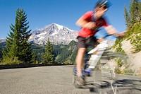Young man mountain biking on road.