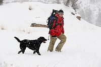 Side view of a mid adult man wearing a red jacket and backpack walking in the snow with a black dog in Bend, Oregon.