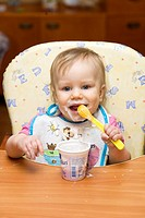 One year old dirty baby girl eating yogurt using spoon