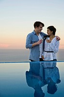 Couple standing at edge of infinity pool, enjoying champagne
