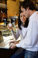 Couple using laptop computer in cafe