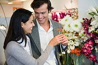 Couple looking at artificial flowers together