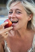 Mature woman biting into apple