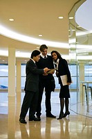 Business executives standing together discussing document