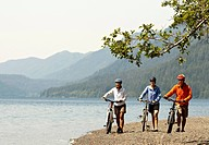 Mountain bikers enjoying views of the lake and hillsides covered in trees.
