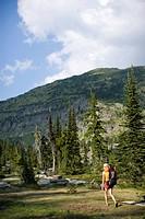 Adult woman hiking through an alpine meadow.