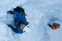 A professional female climber is belayed from below while ice climbing a frozen waterfall in Colorado.